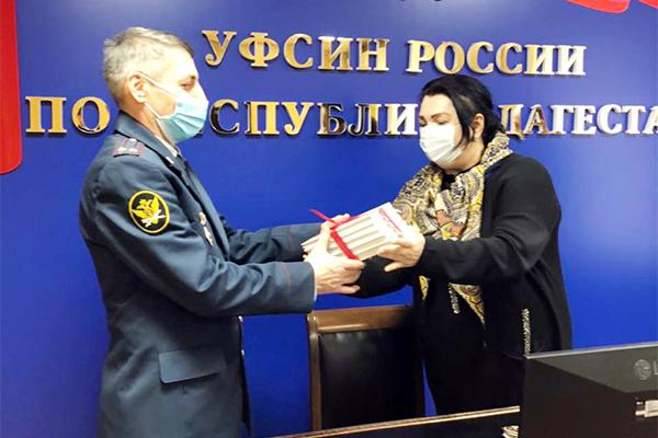 Начальник ОВСРО УФСИН получает книги от представителя Миннаца РД