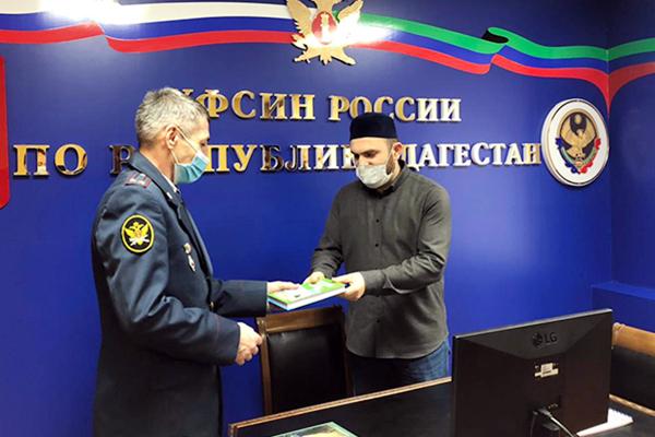Начальник ОВСРО УФСИН получает книги от представителя Муфтията РД
