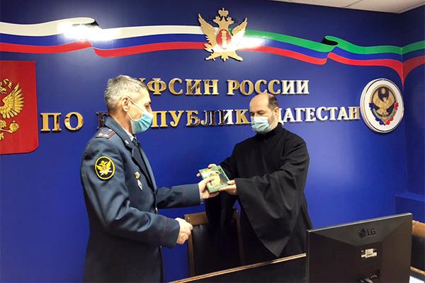 Начальник ОВСРО УФСИН получает книги от представителя РПЦ